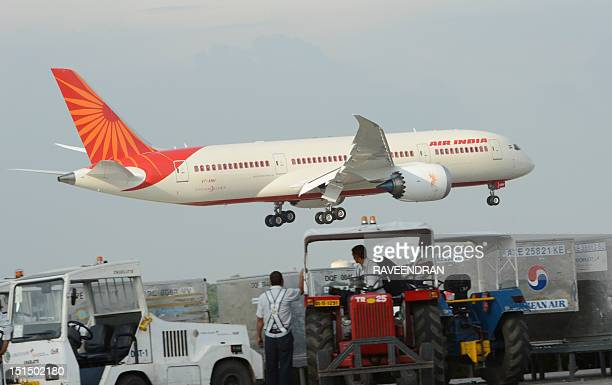 Indian ground personnel look on as Air India's first Boeing 787 Dreamliner from Charleston USA arrives at Indira Gandhi International airport's...