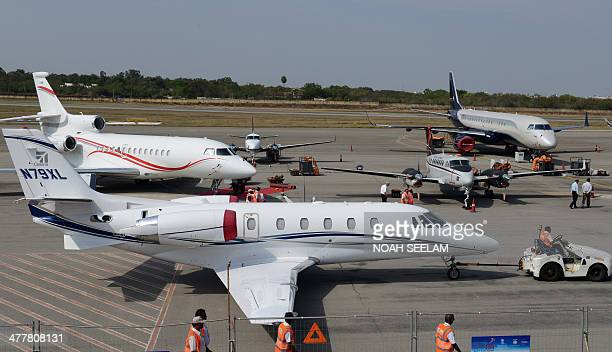 Indian groundstaff move a Cessna N79XL aircraft to be parked on display at Begumpet Airport in Hyderabad on March 11 ahead of The India Aviation 2014...