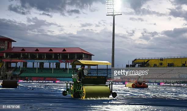 Indian groundstaff use machines to disperse rainwater from covers on the playing surface ahead of the World T20 cricket tournament qualifying match...