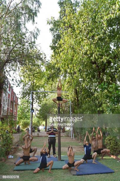 Indian gymnast coach Jayeshbhai Kacha and his young students pray before practicing Mallakhamb at CN Sports Academy in Ahmedabad on June 10 ahead of...