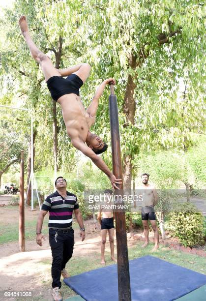 Indian gymnast coach Jayeshbhai Kacha and his young students take part in a Mallakhamb practice session at CN Sports Academy in Ahmedabad on June 10...