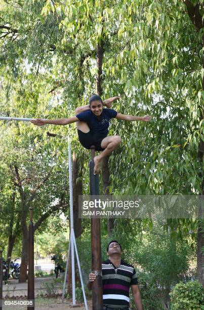 Indian gymnastics coach Jayeshbhai Kacha watches one of his young students as she takes part in a Mallakhamb practice session at CN Sports Academy in...