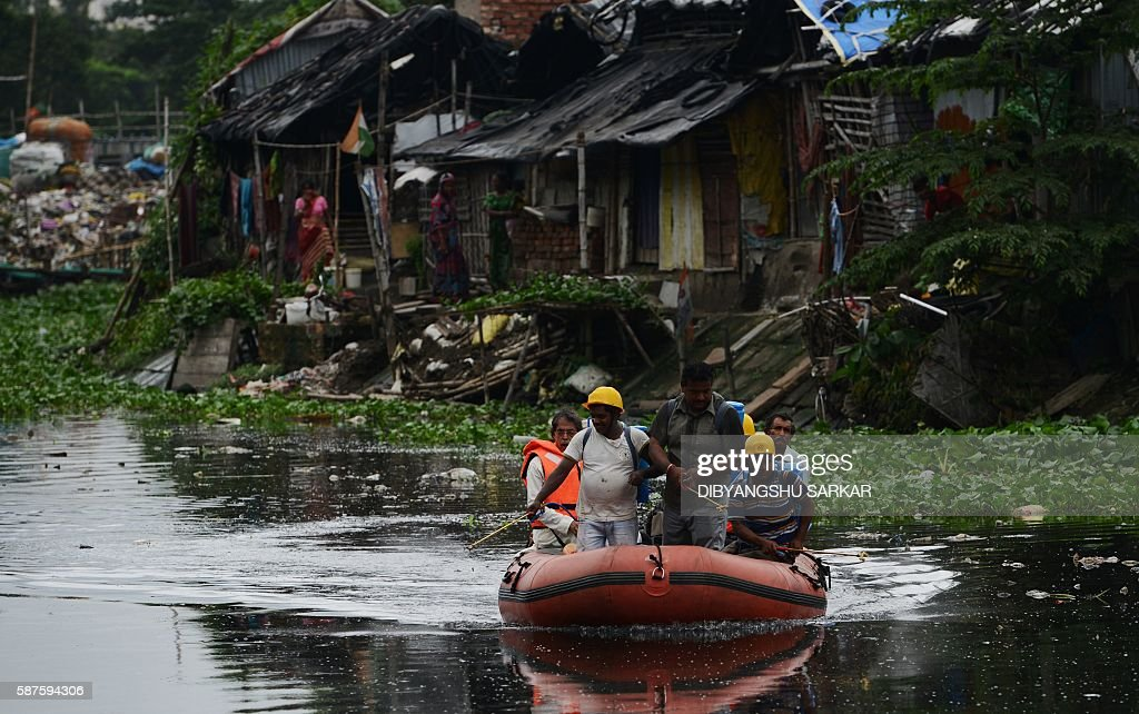 Indian health and municipal workers use a boat to help distribute pestcontrol chemicals to kill mosquitoes and larvae on a waterway in Kolkata on...