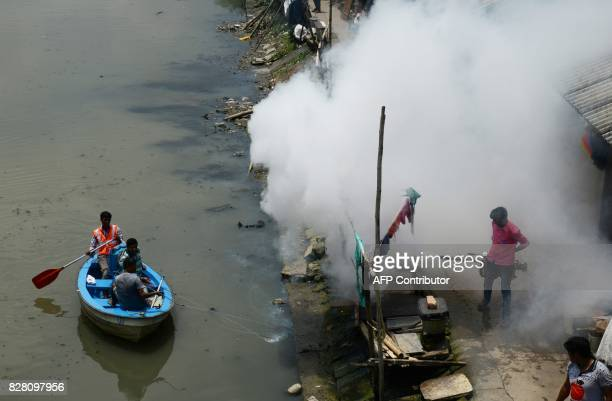 Indian health and municipal workers use a boat to help distribute pestcontrol chemicals to kill mosquitoes and larvae in Kolkata on August 9 2017...