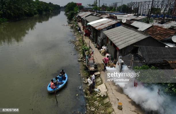 TOPSHOT Indian health and municipal workers use a boat to help distribute pestcontrol chemicals to kill mosquitoes and larvae in Kolkata on August 9...