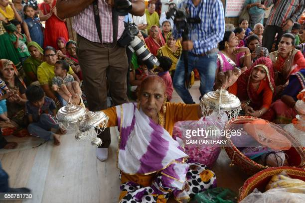Indian hijras show ornaments made from Silver to be gifted to the Paanchdev Mandir during a religious procession in Gandhinaar some 30 km from...