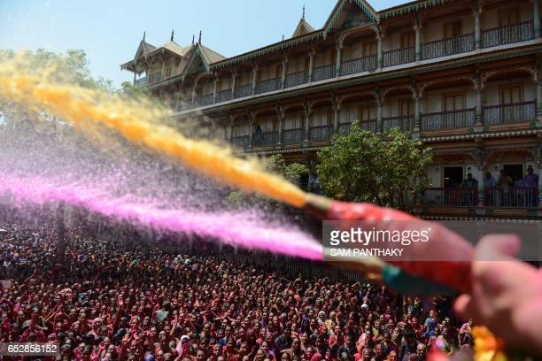 TOPSHOT Indian Hindu devotees are sprayed with coloured water by heir to the Kalupur Swaminarayan Temple Lalji Maharaj Shri Vrajendraprasdaji Maharaj...