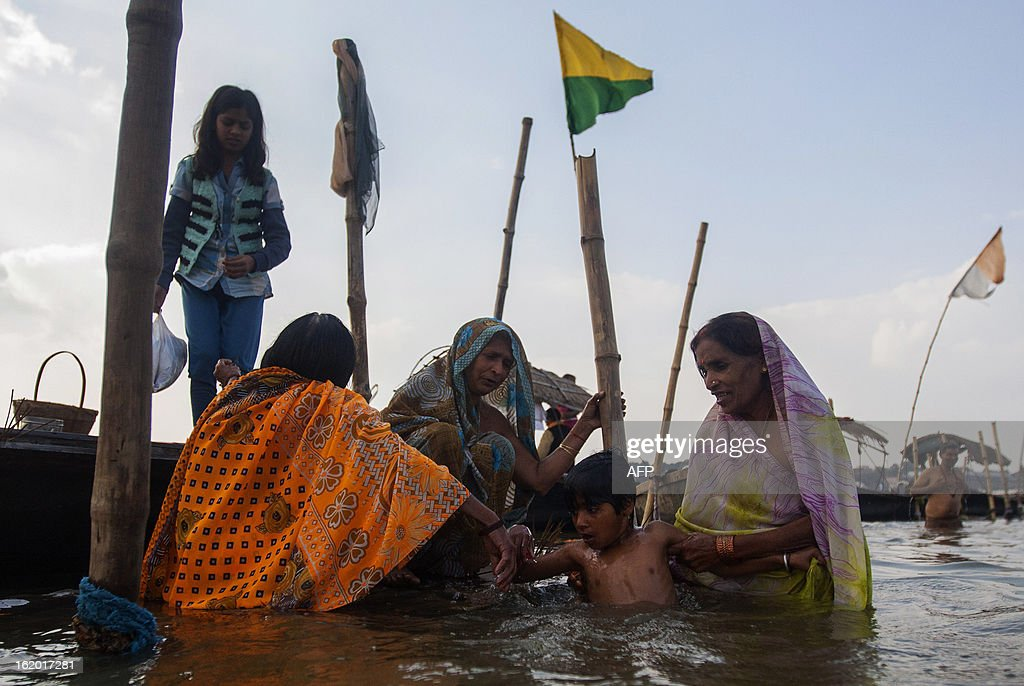 Indian Hindu devotees bathe a young boy in the Sangam or confluence of the Yamuna, Ganges and mythical Saraswati rivers at the Kumbh Mela in Allahabad on February 18, 2013. The Kumbh Mela in the town of Allahabad will see up to 100 million worshippers gather over 55 days to take a ritual bath in the holy waters, believed to cleanse sins and bestow blessings. AFP PHOTO/ Andrew Caballero-Reynolds