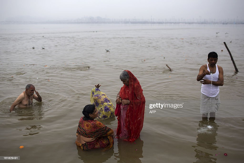Indian Hindu devotees bathe at the Sangam or confluence of the Yamuna, Ganges and mythical Saraswati rivers at the Kumbh Mela in Allahabad on February 17, 2013. The Kumbh Mela in the town of Allahabad will see up to 100 million worshippers gather over 55 days to take a ritual bath in the holy waters, believed to cleanse sins and bestow blessings. AFP PHOTO/ Andrew Caballero-Reynolds