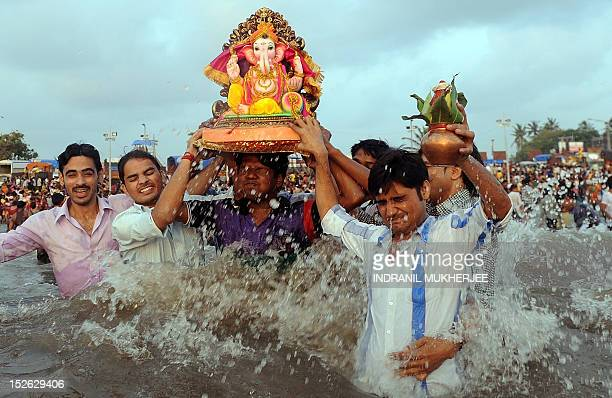 Indian Hindu devotees carry an idol of elephantheaded Hindu god Ganesha as they chant mantrasreligious hymns during immersion at the iconic Juhu...