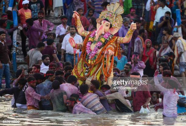 TOPSHOT Indian Hindu devotees carry an idol of the elephantheaded Hindu god Lord Ganesha for immersion in a pool near Sangam in Allahabad on...
