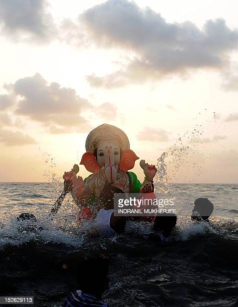 Indian Hindu devotees carrying an idol of elephantheaded Hindu god Ganesha brave a high wave during immersion at the iconic Juhu Chowpatty beach on...