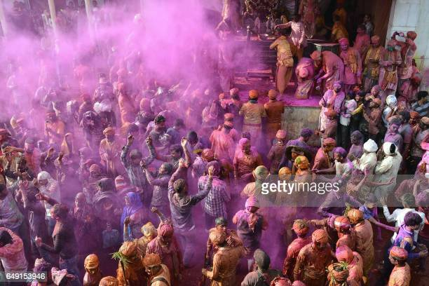 TOPSHOT Indian Hindu devotees celebrate Holi the spring festival of colours during a traditional gathering at Nandgaon village in Uttar Pradesh state...