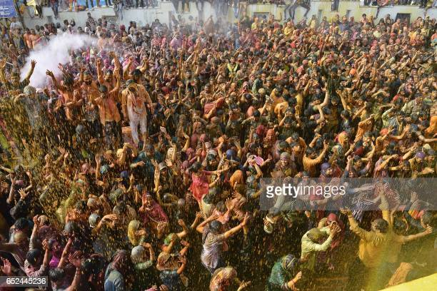 TOPSHOT Indian Hindu devotees celebrate Holi the spring festival of colours in Mathura in Uttar Pradesh state on March 12 2017 Holi is observed in...