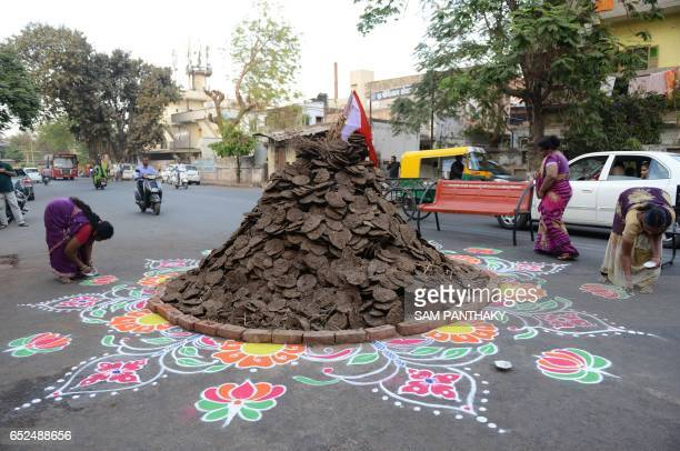 Indian Hindu devotees decorate the ground around a traditional 'Holika' made out of cakes of cow dung and coconuts in Ahmedabad on March 12 2017...