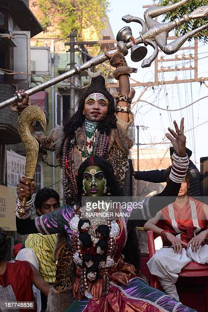 Indian Hindu devotees dressed as Lord Shiva and the goddess Kali Mata participate in a procession in Amritsar on November 12 on the occasion of the...