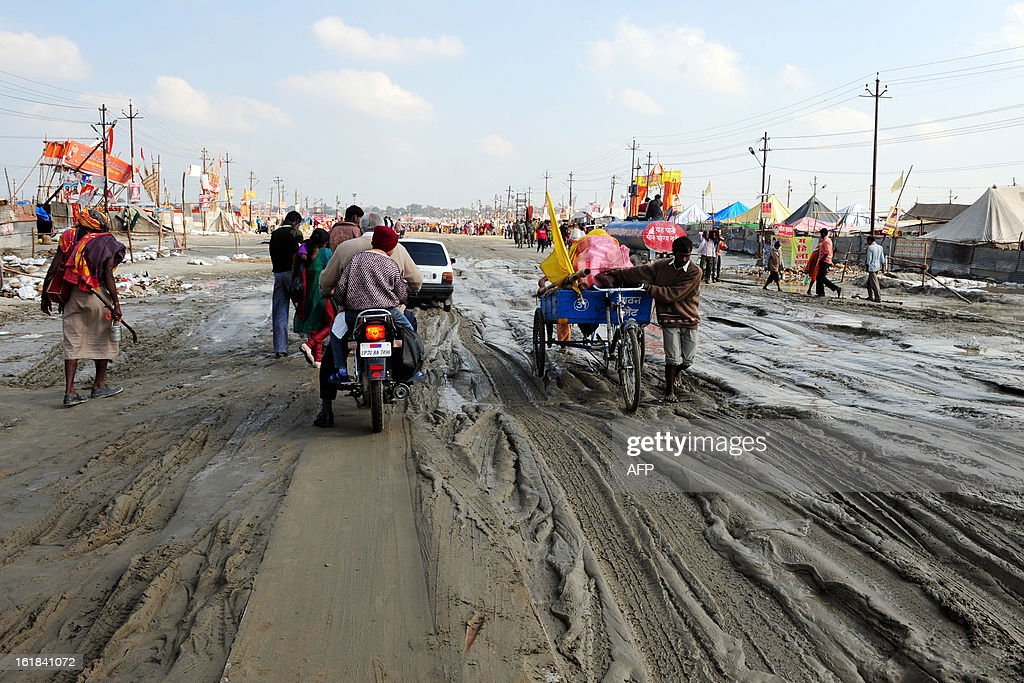 Indian Hindu devotees drive through mud as they leave after completing their stay for the Maha Kumbh festival in Allahabad on February 17, 2013. The Kumbh Mela, which ends in March and attracts millions of worshippers to bathe in the holy waters of the Sangam, takes place every 12 years in Allahabad while smaller events are held every three years in other locations around India. AFP PHOTO/ SANJAY KANOJIA