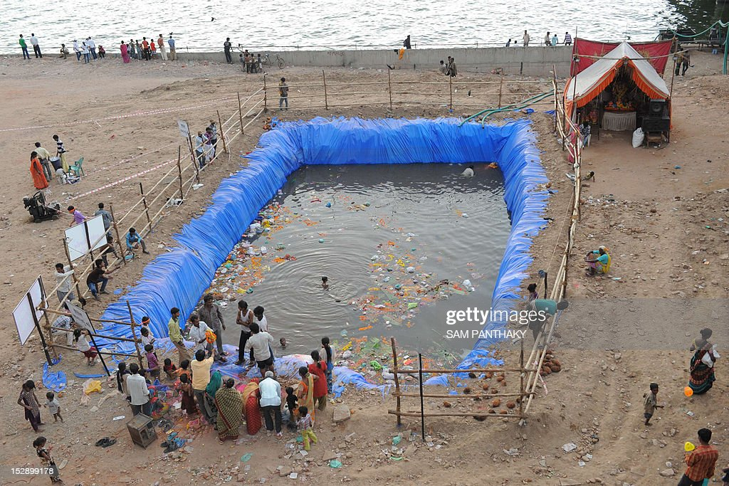Indian Hindu devotees gather at an artificial pond, dug for the ongoing Ganesh Chathurthi festival to help control pollution and waste, along the banks of the Sabarmati river in Ahmedabad on September 28, 2012. Hindu devotees bring home idols of Lord Ganesha during the 'Ganesh Chaturthi' in order to invoke his blessings for wisdom and prosperity, during the eleven day long festival which culminates with the immersion of the idols AFP PHOTO / Sam PANTHAKY