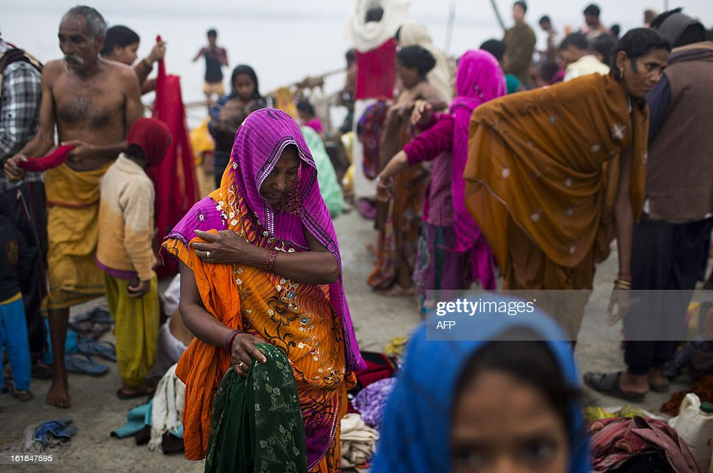 Indian Hindu devotees get dressed after bathing at the Sangam or confluence of the Yamuna, Ganges and mythical Saraswati rivers at the Kumbh Mela in Allahabad on February 17, 2013. The Kumbh Mela in the town of Allahabad will see up to 100 million worshippers gather over 55 days to take a ritual bath in the holy waters, believed to cleanse sins and bestow blessings. AFP PHOTO/ Andrew Caballero-Reynolds