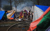 Indian Hindu devotees go about their daily business at their tents pitched for the Magh Mela festival in Allahabad on January 18 2014 The Magh Mela...