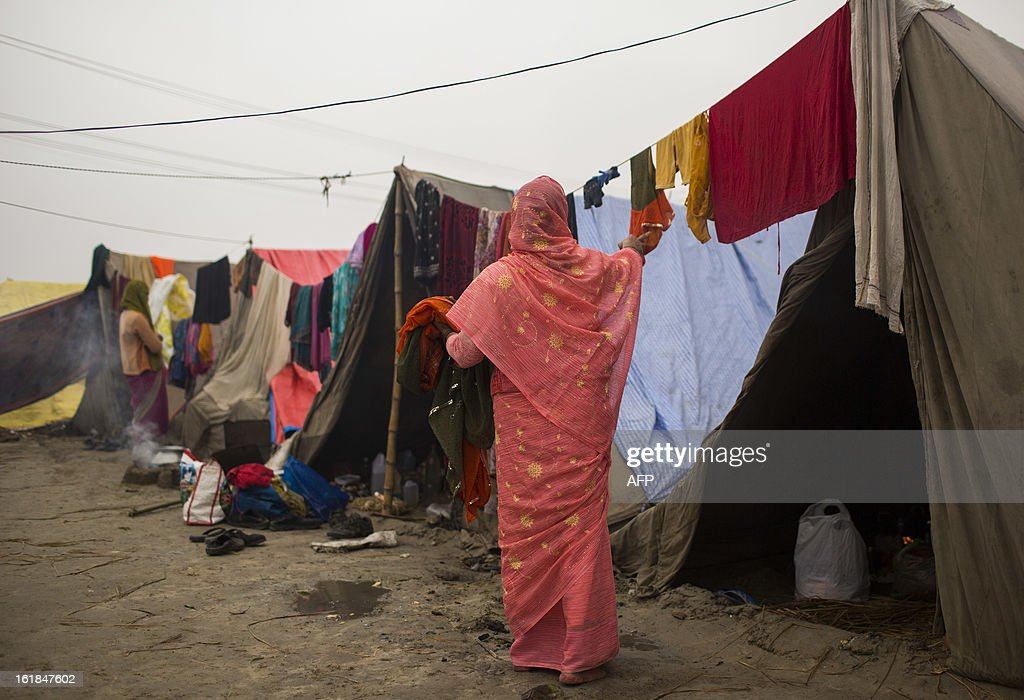 Indian Hindu devotees hang clothing that got wet from rains the day before at the Kumbh Mela in Allahabad on February 17, 2013. The Kumbh Mela in the town of Allahabad will see up to 100 million worshippers gather over 55 days to take a ritual bath in the holy waters, believed to cleanse sins and bestow blessings. AFP PHOTO/ Andrew Caballero-Reynolds