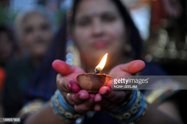 Indian Hindu devotees hold candles as offer prayers to the sun during the Chhath Festival on the banks of the Hussain Sagar lake in Hyderabad on...