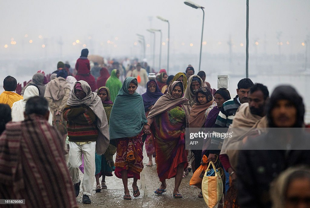 Indian Hindu devotees hold hands as they cross a pontoon bridge over the Sangam or confluence of the Yamuna, Ganges and mythical Saraswati rivers during the Kumbh Mela in Allahabad on February 17, 2013. The Kumbh Mela in the town of Allahabad will see up to 100 million worshippers gather over 55 days to take a ritual bath in the holy waters, believed to cleanse sins and bestow blessings. AFP PHOTO/ Andrew Caballero-Reynolds