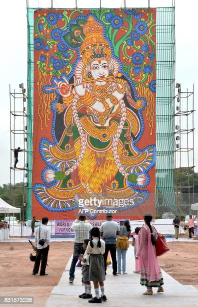 Indian Hindu devotees look at a 60foot painting of Lord Krishna on display at the Palace Grounds during Krishna Janmashtami celebrations in Bangalore...