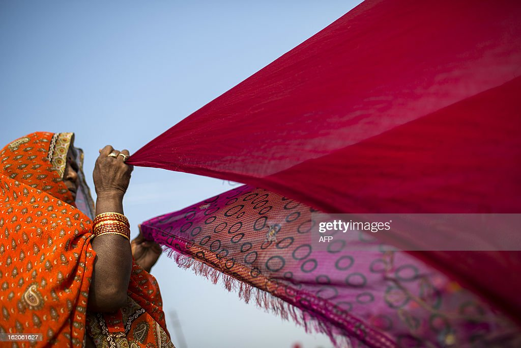 Indian Hindu devotees look on as they wait for their saris to dry near their tents at the Kumbh Mela in Allahabad on February 19, 2013. The Kumbh Mela in the town of Allahabad will see up to 100 million worshippers gather over 55 days to take a ritual bath in the holy waters, believed to cleanse sins and bestow blessings. AFP PHOTO/ Andrew Caballero-Reynolds