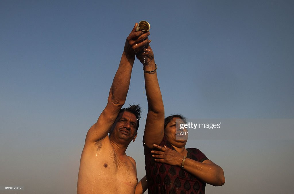 Indian Hindu devotees make an offering as they bathe in the Sangam or confluence of the Yamuna, Ganges and mythical Saraswati rivers at the Kumbh Mela in Allahabad on February 18, 2013. The Kumbh Mela in the town of Allahabad will see up to 100 million worshippers gather over 55 days to take a ritual bath in the holy waters, believed to cleanse sins and bestow blessings. AFP PHOTO/ Andrew Caballero-Reynolds