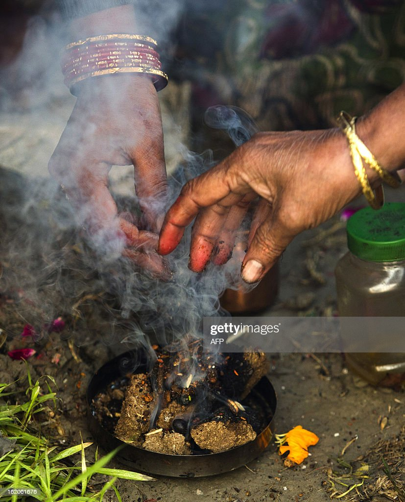 Indian Hindu devotees make an offering near the Sangam or confluence of the Yamuna, Ganges and mythical Saraswati rivers at the Kumbh Mela in Allahabad on February 19, 2013. The Kumbh Mela in the town of Allahabad will see up to 100 million worshippers gather over 55 days to take a ritual bath in the holy waters, believed to cleanse sins and bestow blessings. AFP PHOTO/ Andrew Caballero-Reynolds