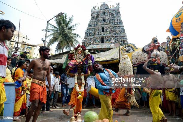 Indian Hindu devotees of Goddess Angala Parameshwari dance carrying a figurine of the deity during the culmination of the 'Mayana Kollai' festival in...