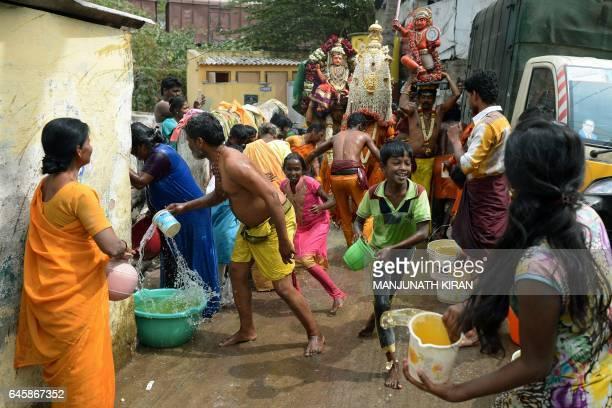 Indian Hindu devotees of Goddess Angala Parameshwari splash turmeric water on each other as they celebrate the culmination of the 'Mayana Kollai'...