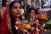 Indian Hindu devotees offer prayer during the 'Chhat Puja 'while standing in the sarover of the Durgiana temple in Amritsar on November 8 2013...