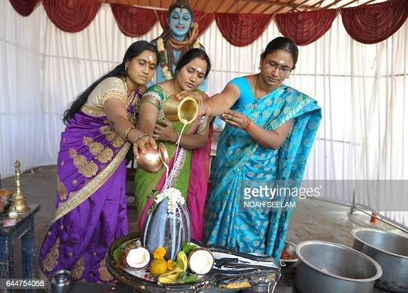 TOPSHOT Indian Hindu devotees offer prayers by pouring milk to a Shiva Lingam a stone sculpture representing the phallus of Hindu god Lord Shiva to...