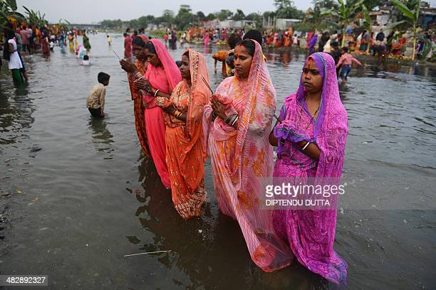 Indian Hindu devotees offer prayers during the Chaiti Chhath festival in Siliguri on April 5 2014 Devotees pay obeisance to both the rising and the...
