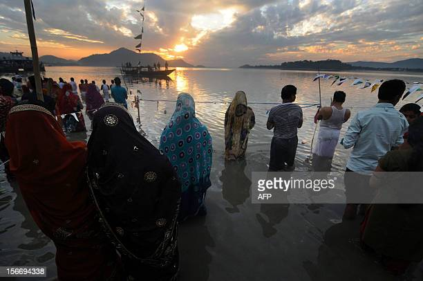 Indian Hindu devotees offer prayers to the sun during The Chhat Festival on the banks of the River Brahmaputra in Guwahati on November 19 2012 The...