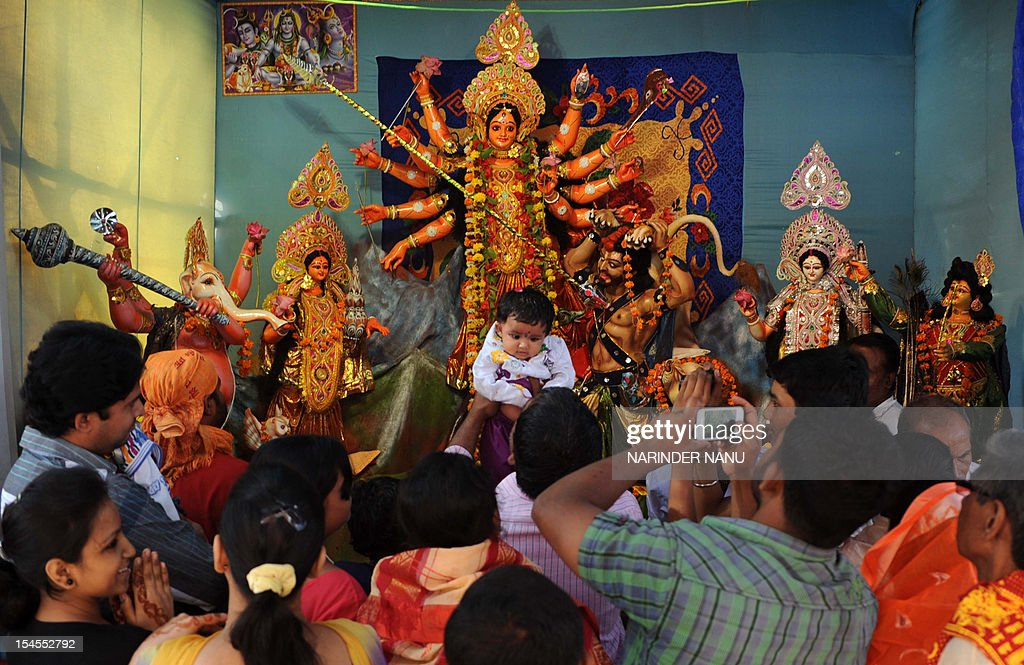 Indian Hindu devotees pay their respects in the front of an idol of Hindu goddess Durga during the Durga Puja festival in Amritsar on October 22, 2012. The five-day period of worship of Durga, who is attributed as the destroyer of evil, commenced on October 20.