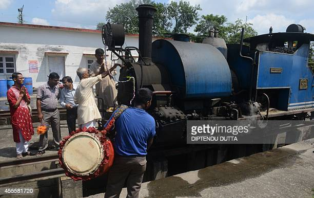 Indian Hindu devotees perform a ritual at the Toy Train engine at a workshop in Siliguri on September 17 2014 on the occasion of Viswakarma Puja...