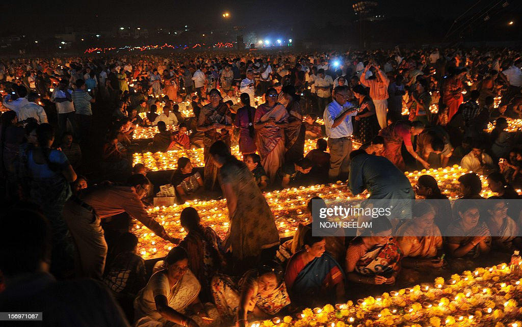 Indian Hindu devotees perform a ritual by lighting diyas - earthen lamps - on the occasion of Karthika month in Hyderabad on November 26, 2012. Karthika month is one of the most auspicious months in the lunar calendar which begins on the day after Diwali, the Festival of Lights and ends after 30 days. It is considered very sacred by the devotees of Lord Shiva and Lord Vishnu. AFP PHOTO / Noah SEELAM