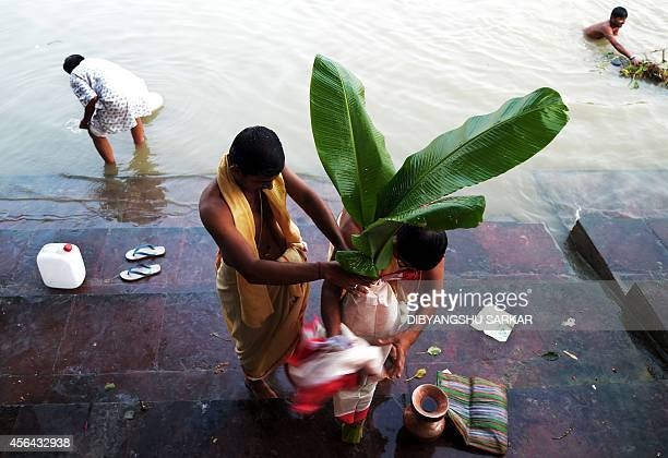 Indian Hindu devotees perform a ritual with a banana tree wrapped in a sari symbolising the wife of the Hindu god Ganesha on the river Ganges during...