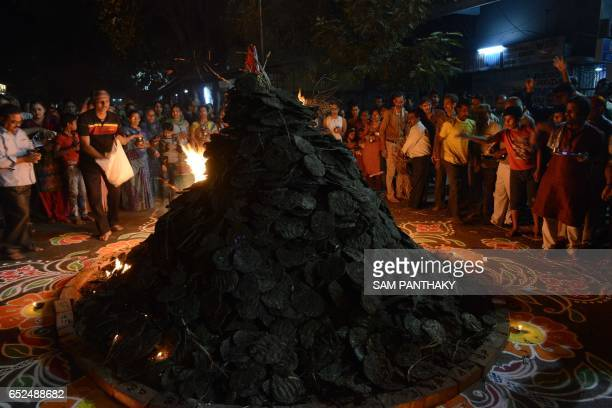 Indian Hindu devotees perform rituals as they ignite a 'Holika' made out of ecofriendly cowdung cakes and coconuts in Khokhra area of Ahmedabad on...
