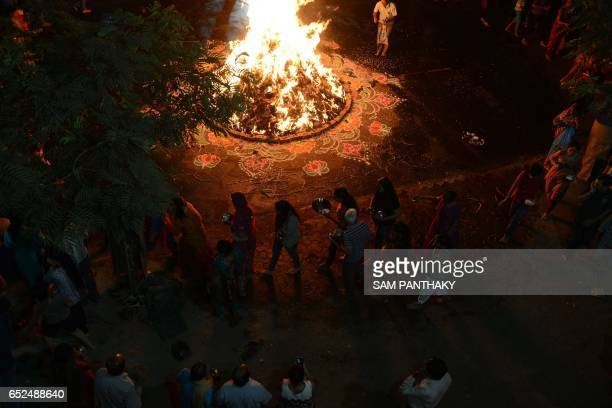 Indian Hindu devotees perform rituals as they walk around a traditional 'Holika' made out of cakes of cow dung and coconuts in Ahmedabad on March 12...