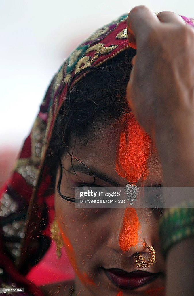 Indian Hindu devotees perform rituals during Chhat Puja while standing in the river in Kolkata on November 20, 2012. Devotees pay obeisance to both the rising and the setting sun during the Chhath festival when people express their thanks and seek the blessings of the forces of nature, mainly the Sun and the River. AFP PHOTO/Dibyangshu SARKAR
