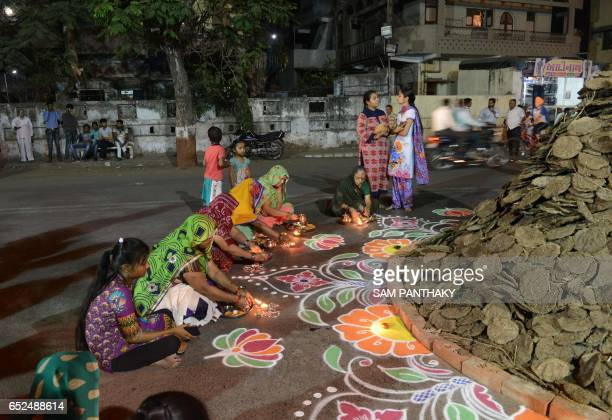 Indian Hindu devotees perform rituals next to a traditional 'Holika' made out of cakes of cow dung and coconuts in Ahmedabad on March 12 2017 Holika...