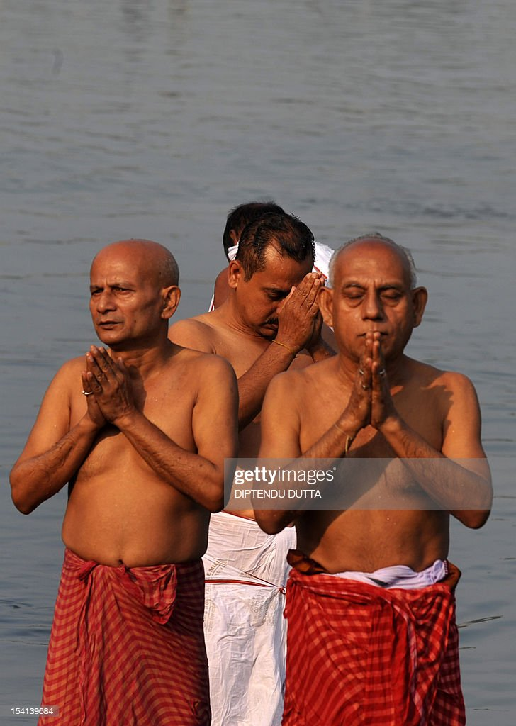 Indian Hindu devotees perform 'Tarpan', a ritual to pay obesience to one's forefathers, on the last day of 'Pitrupaksh' - days for offering prayers to ancestors - on the banks of the river Mahananda in Siliguri on October 15, 2012. In Hindu mythology this day is also called 'Mahalaya' and describes the day when the gods created the ten armed goddess Durga to destroy the demon king Asura who plotted to drive out the gods from their kingdom. The five-day period of worship of Durga, who is attributed as the destroyer of evil, commences on October 20. AFP PHOTO/Diptendu DUTTA