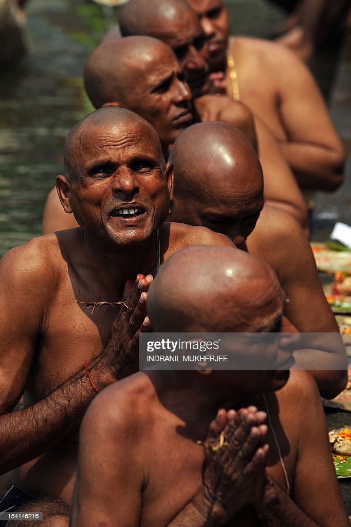 Indian Hindu devotees perform 'Tarpan', a ritual to pay obesience to one's forefathers, on the last day for offering prayers to ancestors called 'Pitrupaksh' in Mumbai on October 15, 2011. In Hindu mythology, this day is also called 'Mahalaya' and described as the day when the gods created the ten armed goddess Durga to destroy the demon king Asura who plotted to drive out the gods from their kingdom. The five-day period of worship of Durga, who is attributed as the destroyer of evil, commences on October 20. AFP PHOTO/Indranil MUKHERJEE