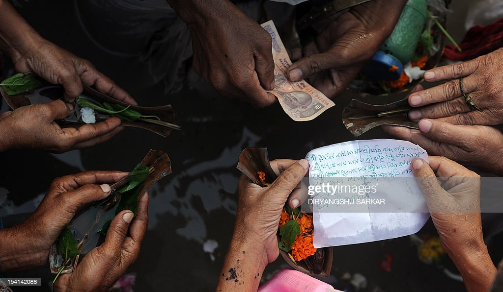 Indian Hindu devotees perform 'Tarpan', rituals to pay obesience to one's forefathers on the last day of 'Pitrupaksh' - days for offering prayers to ancestors, on the banks of the holy river Ganga in Kolkata on October 15, 2012. In Hindu mythology this day is also called 'Mahalaya' and describes the day when the gods created the ten armed goddess Durga to destroy the demon king Asura who plotted to drive out the gods from their kingdom. The five-day period of worship of Durga, who is attributed as the destroyer of evil, commences on October 20. AFP PHOTO/Dibyangshu SARKAR