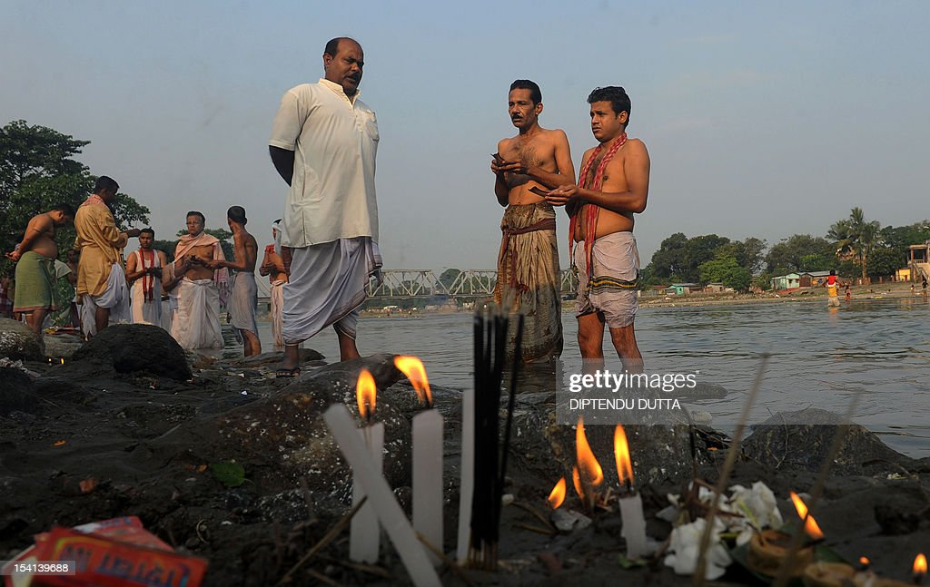 Indian Hindu devotees perfrom 'Tarpan', a ritual to pay obesience to one's forefathers, on the last day of 'Pitrupaksh' - days for offering prayers to ancestors - on the banks of the river Mahananda in Siliguri on October 15, 2012. In Hindu mythology this day is also called 'Mahalaya' and describes the day when the gods created the ten armed goddess Durga to destroy the demon king Asura who plotted to drive out the gods from their kingdom. The five-day period of worship of Durga, who is attributed as the destroyer of evil, commences on October 20. AFP PHOTO/Diptendu DUTTA