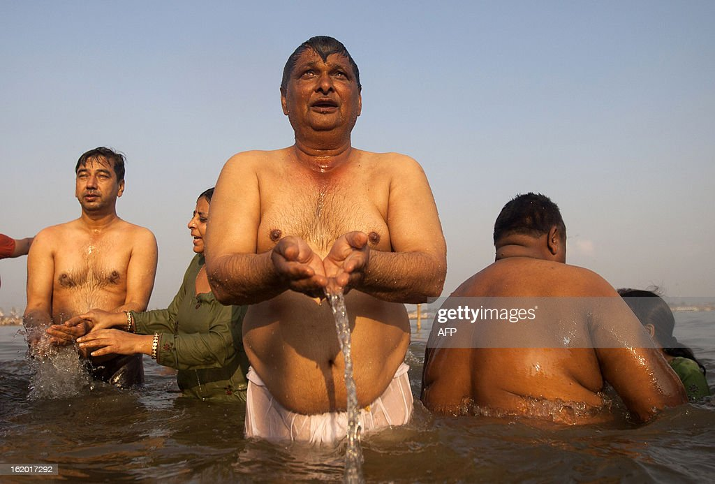 Indian Hindu devotees pray as they bathe in the Sangam or confluence of the Yamuna, Ganges and mythical Saraswati rivers at the Kumbh Mela in Allahabad on February 18, 2013. The Kumbh Mela in the town of Allahabad will see up to 100 million worshippers gather over 55 days to take a ritual bath in the holy waters, believed to cleanse sins and bestow blessings. AFP PHOTO/ Andrew Caballero-Reynolds